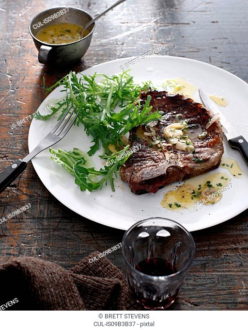Bistro meal of T-Bone Steak with bercy sauce and red wine on table