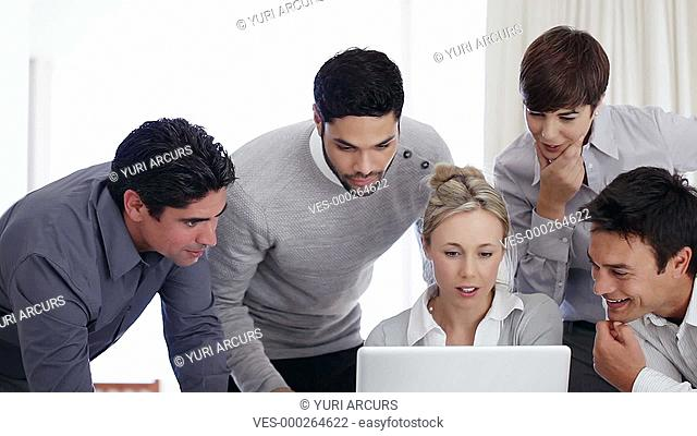 Group of businesspeople gathered round a colleague's computer discussing their plan