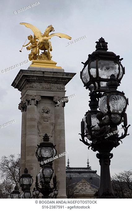 Paris, France - Street lamps and golden statue on Alexandre III bridge over river Seine