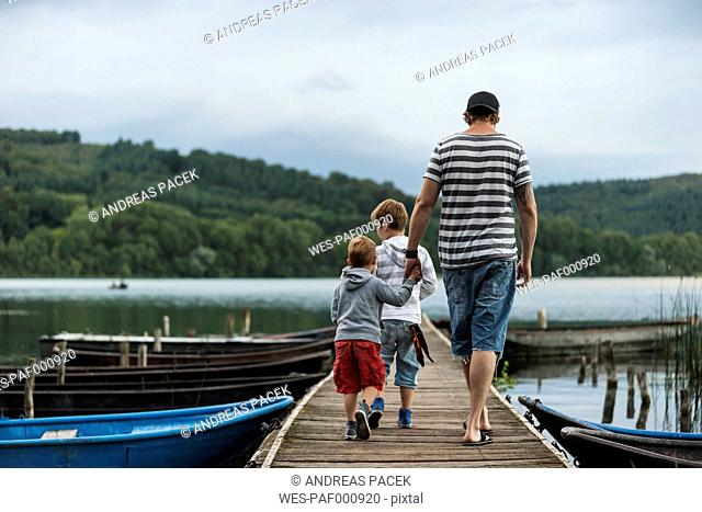 Germany, Rhineland-Palatinate, Laacher See, father walking with two sons on jetty