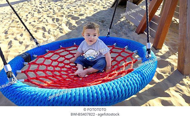 little boy sitting in a nest swing, Netherlands