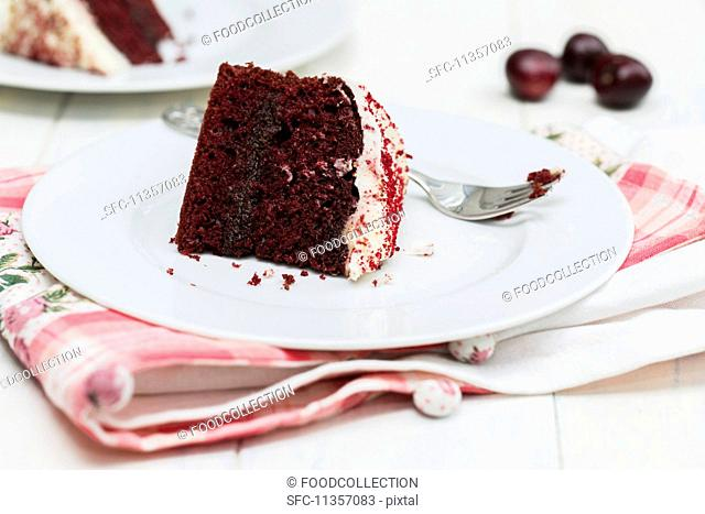 A slice of Red Velvet cake on a plate with a fork