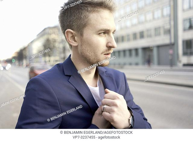business man at street, wearing blazer, freezing, cold temperatures, in city Munich, Germany