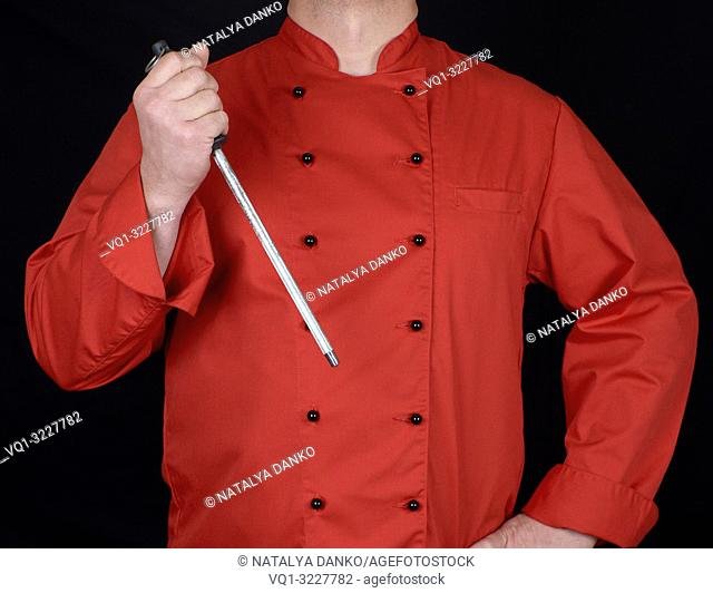chef in red uniform holds knife sharpening tool, black background