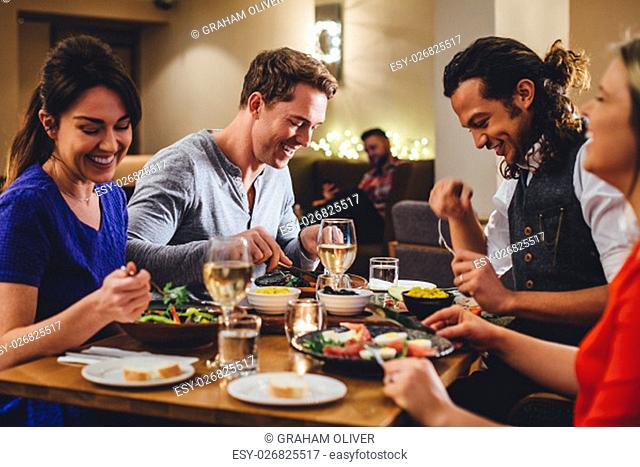 Group of friends enjoying an evening meal with wine at a restaurant