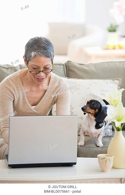Dachshund watching Chinese woman using laptop in living room