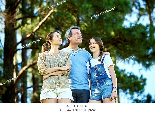 Family standing together in forest