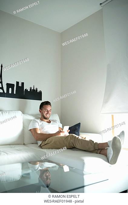Smiling young man relaxing at home with his smartphone