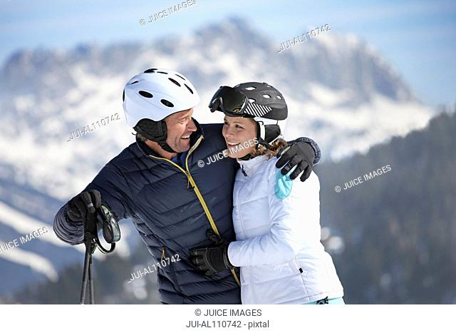 Mature man with arm around woman on ski slope
