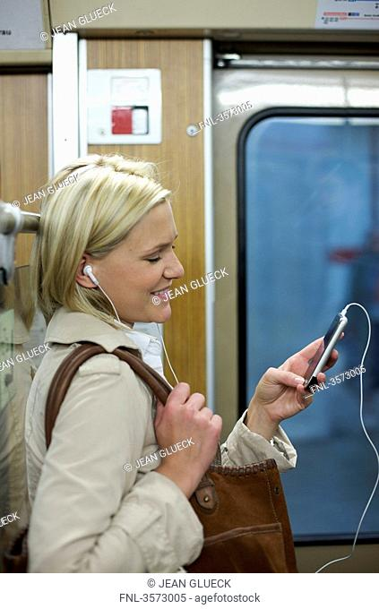 Woman listening to music on cell phone in the subway, profile