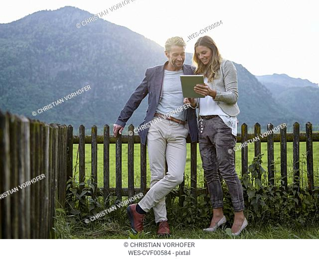 Man and woman sharing tablet in rural landscape