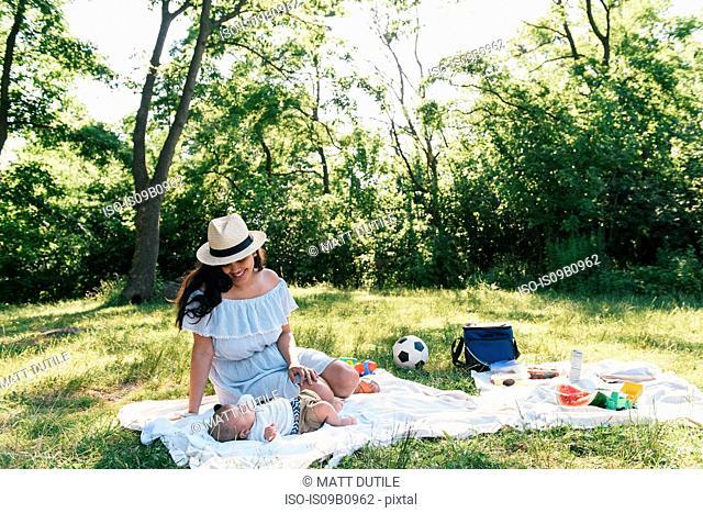 Mid adult woman and baby son on picnic blanket in Pelham Bay Park, Bronx, New York, USA