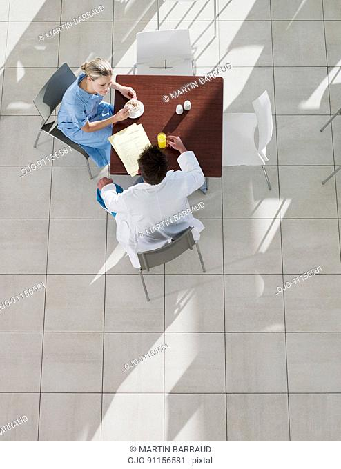 Doctor and nurse talking in cafeteria