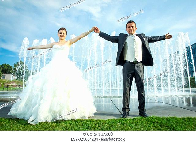 The bride and groom holding hands widespread and looking at camera while standing in front of a water spray fountain in Zagreb, Croatia