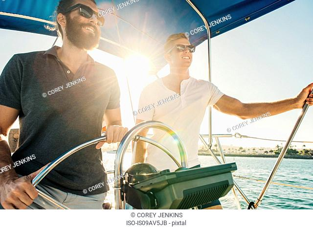 Man steering wheel of sailboat, San Diego Bay, California, USA