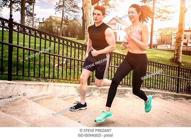 Young male and female runners running up park stairway