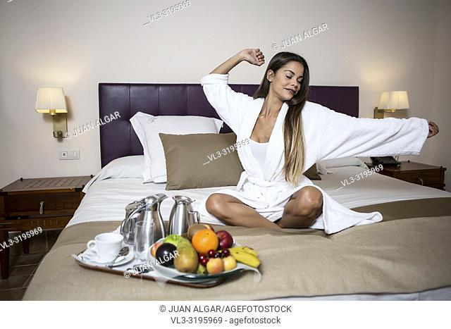 Young pretty woman sitting on bed in morning gown near plate of fresh fruits and coffee set and stretching with closed eyes