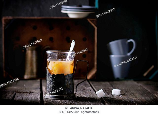 Tea with milk in a vintage tea glass on a rustic wooden table