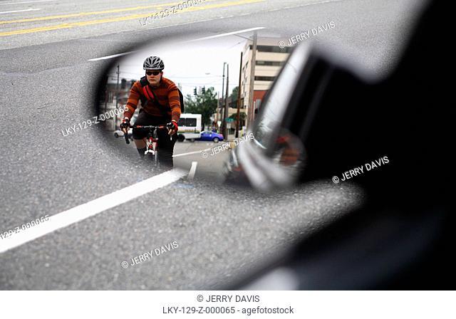 Man riding bike alongside car