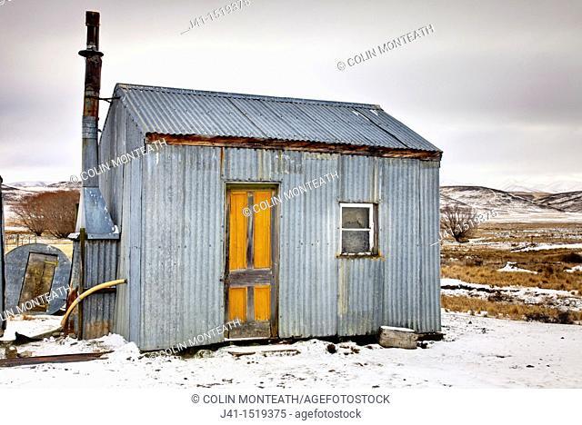 Historic  bach / crib  holiday house used by fishermen, Falls Dam, winter, near St Bathans, Central Otago, South Island, New Zealand