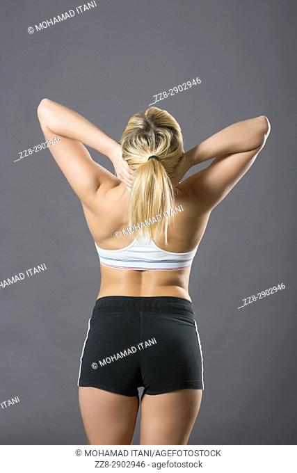 Rear view of a woman wearing sports bra and short hands on head