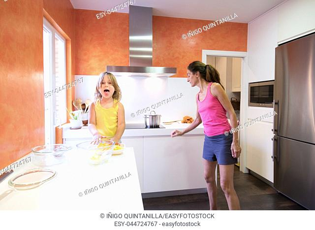 Four years old blonde happy child preparing raw potatoes to cook in the kitchen, looking and sticking out tongue smiling, next to woman mother