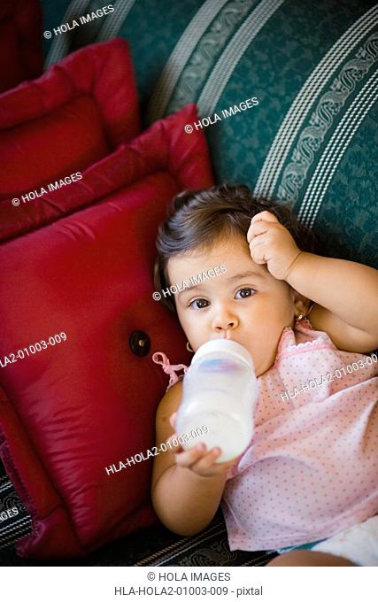 Baby girl drinking milk with a baby bottle