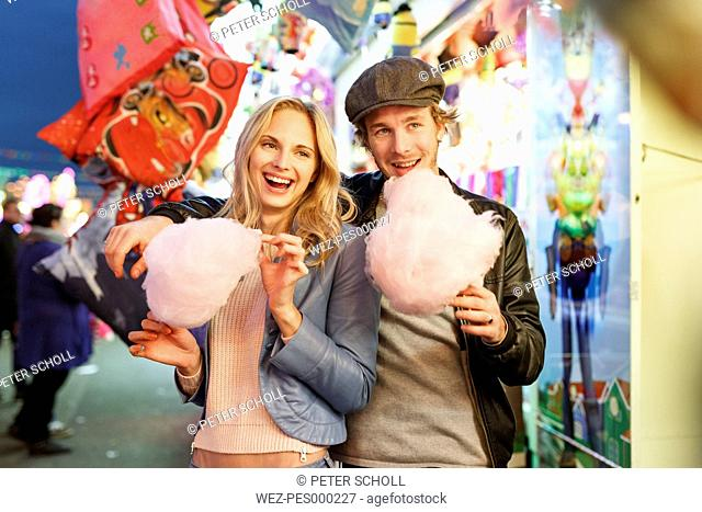Young couple at fun fair eating candy floss