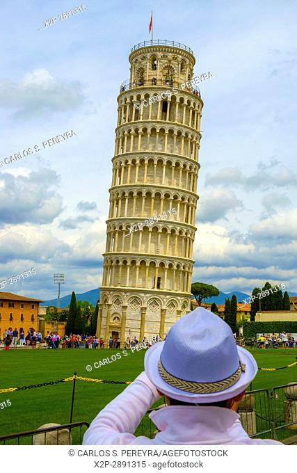 Tourist posing in front of Duomo and Leaning Tower of Pisa, Italy