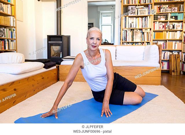Portrait of woman sitting on gym mat in living room
