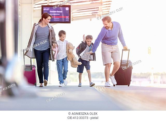 Family walking pulling suitcases at train station