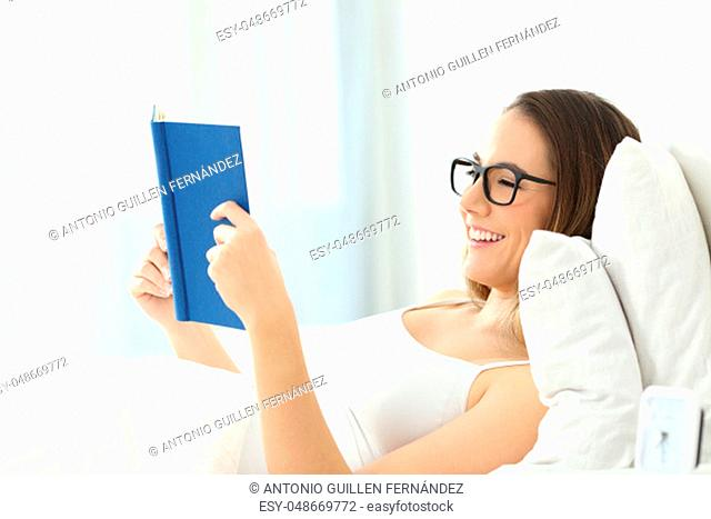 Happy woman wearing eyeglasses reading a book lying on the bed at home or hotel room