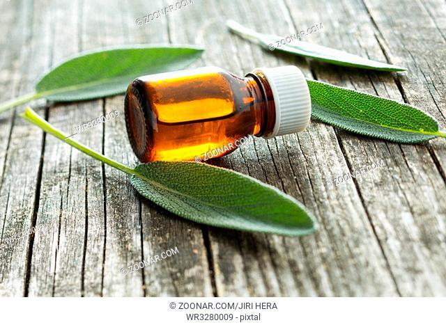 Bottle of essential sage oil on old wooden table. Medicinal herb Salvia officinalis