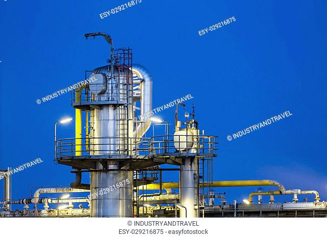 Detail of a distillation tower of a chemical plant and refinery with night blue sky and illumination