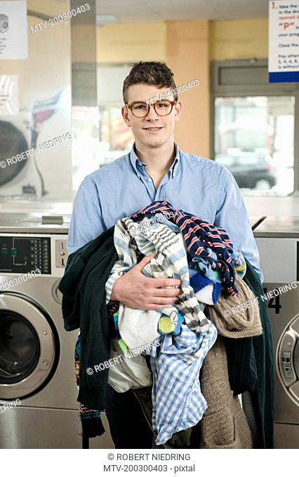 Portrait of young man with laundry, smiling