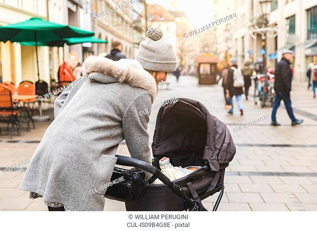 Mid adult woman on city street tending baby daughter in baby carriage