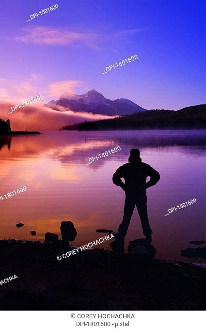 Silhouette of a man at a mountain lake