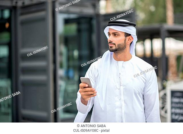 Man wearing traditional middle eastern clothing using smartphone, Dubai, United Arab Emirates
