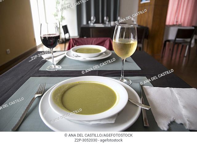 Vegetable soup and cups of wine on table