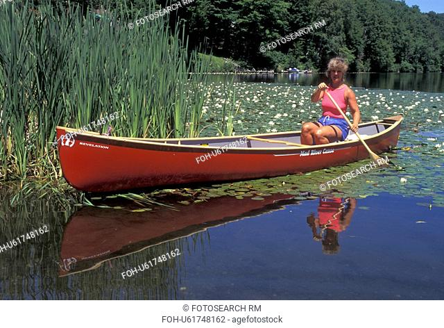 canoeing, canoe, Vermont, VT, Woman paddling a red canoe in the lily pads on Curtis Pond in Maple Corners