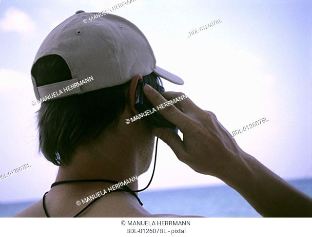 rear view of young man using mobile phone on tropical beach