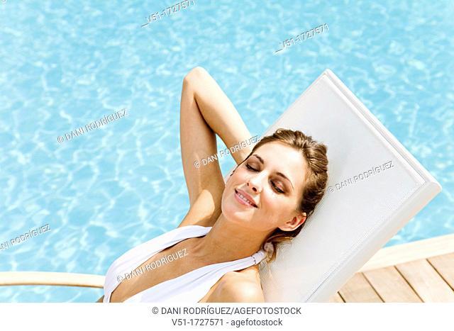 Pretty blonde woman enjoying the sun in a hammock by the pool