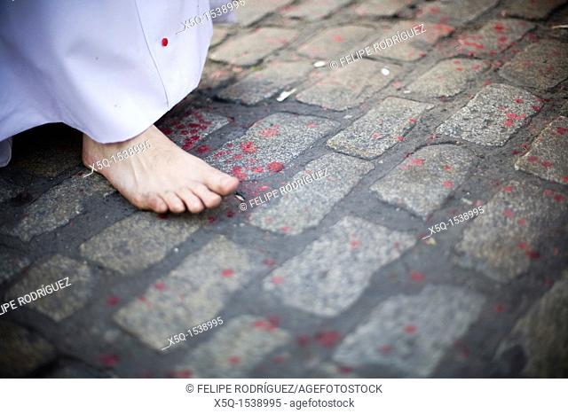 Detail of a barefoot penitent walking on the pavement with melted wax drops, Holy Week 2008, Seville, Spain