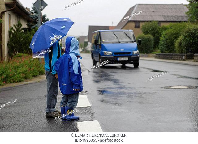 Two children, 4 and 8 years, waiting to cross the street in the rain while a car approaches, Assamstadt, Baden-Wuerttemberg, Germany, Europe