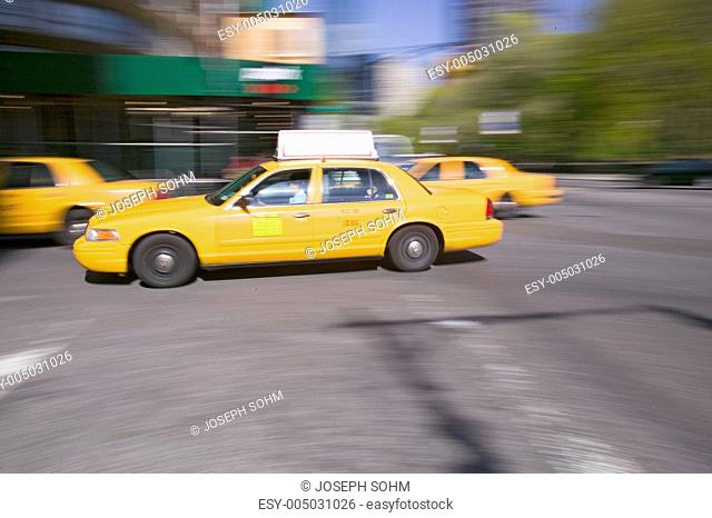 Blurred yellow taxies speed by in Manhattan, New York City, New York