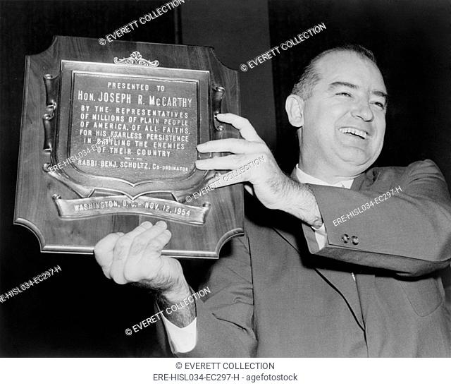 Wisconsin Senator Joseph McCarthy displays a plaque honoring him '…for his fearless persistence in battling the enemies of their country'