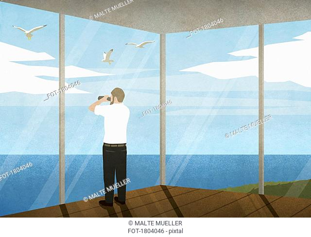 Man with binoculars enjoying ocean view from beach house
