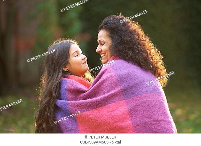 Mother and daughter wrapped in blanket in garden