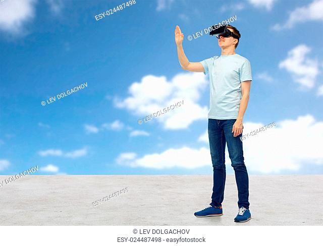 3d technology, virtual reality, entertainment, cyberspace and people concept - happy man with virtual reality headset or 3d glasses playing game and touching...