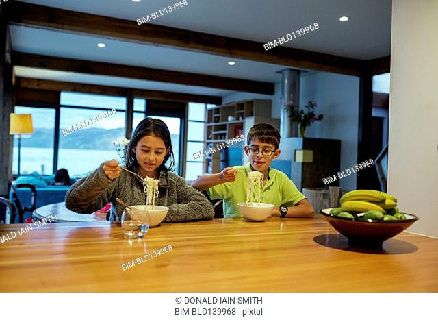 Mixed race children eating noodles at table